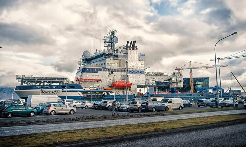 Reykjavik, Iceland - October 13, 2017: cars and ship on cloudy sky. Traffic on road and vessel in port. Transport and. Transportation. Travel or trip and royalty free stock image