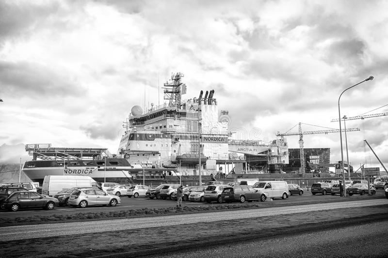 Reykjavik, Iceland - October 13, 2017: cars and ship on cloudy sky. Traffic on road and vessel in port. Transport and. Transportation. Travel or trip and stock photo