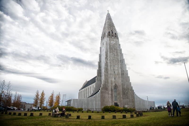 Reykjavik, IJsland - Oktober 12, 2017: hallgrimskirkjakerk en mensen op bewolkte hemel Christendom, godsdienst en geloof Lange st royalty-vrije stock foto's