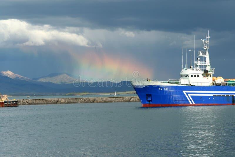 REYKJAVIK ISLAND - JULI 16 2008: Sommarblixt i hamnen med lastfartyg- och altostratusmoln arkivfoton