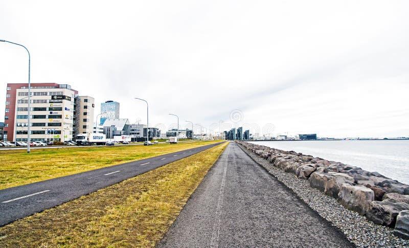 Reykjavik, Islandia - 12 de octubre de 2017: caminos de ciudad a lo largo del mar en el cielo nublado 'promenade' en la playa Lib fotos de archivo