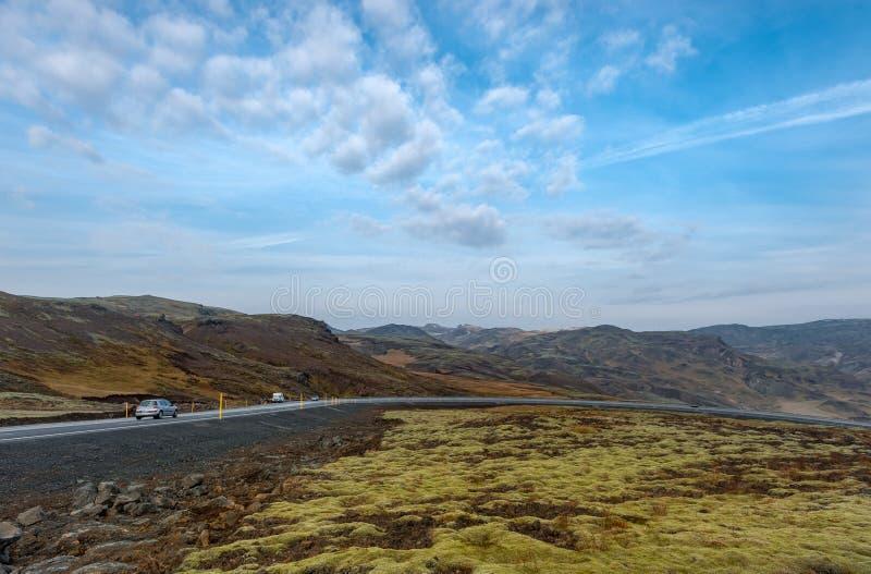REYKJAVIK, ISLANDIA - 15 DE OCTUBRE DE 2016: Paisaje de Islandia con la montaña, el cielo azul y el camino imagen de archivo libre de regalías