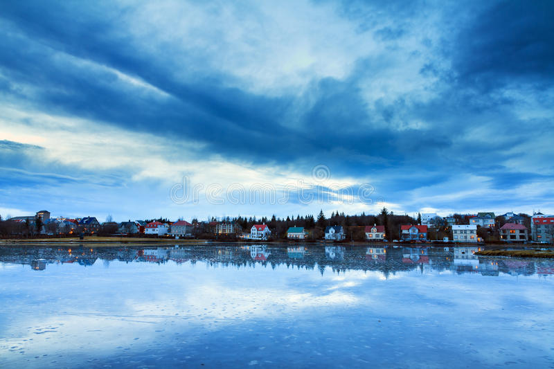 Reykjavik lake Tjornin. Beautiful houses reflected in lake Tjornin in Reykjavik Iceland, during the blue hour in winter royalty free stock images