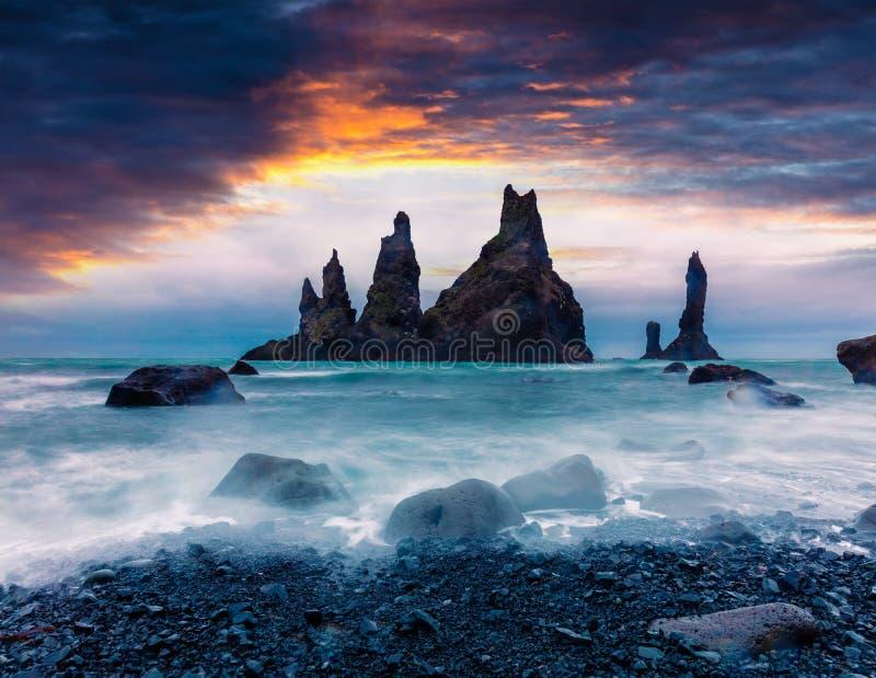 Reynisdrangar峭壁剧烈的海景在大西洋 在南部冰岛,比克的五颜六色的夏天日出村庄地点,E 免版税库存图片