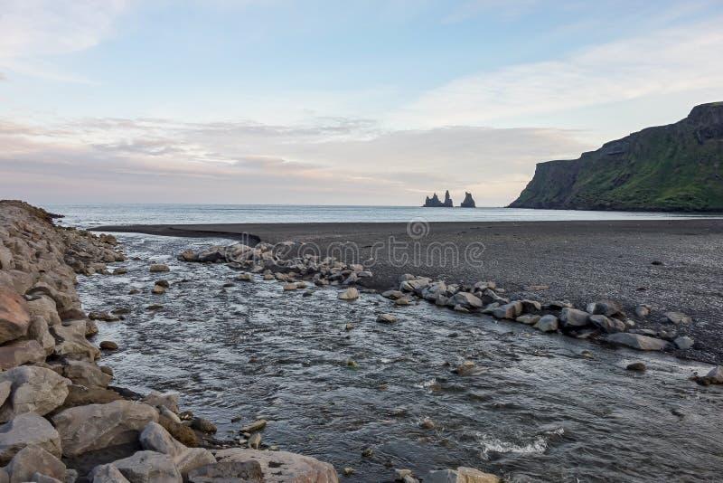 Reynisdrangar basalt rock formation in the Atlantic ocean with a river flowing near Vik i Myrdal, Iceland after sunset stock photos