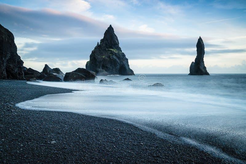 Reynisdrangar. Basalt sea stacks called the Reynisdrangar protrude from the North Atlantic along the coast of southern Iceland. Legend has it that three trolls royalty free stock photo
