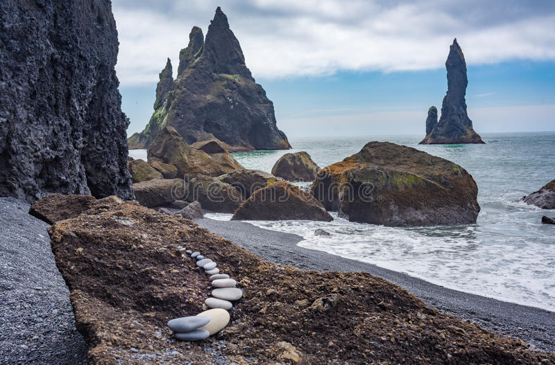 Reynisdrangar basalt sea stacks, Iceland. The black beach Reynisfjara with the framing the Reynisdrangar basalt sea stacks in the background. Legend says that stock photos