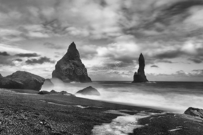 Reynisdrangar. Are basalt sea stacks situated under the mountain Reynisfjall near the village Vík í Mýrdal, southern Iceland which is framed by a black stock photos