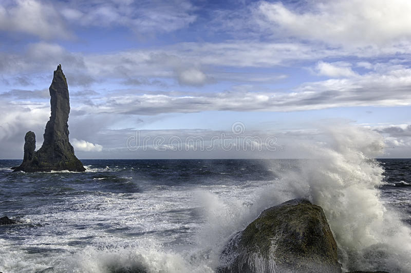 Reynisdrangar. Are basalt sea stacks situated under the mountain Reynisfjall near the village Vík í Mýrdal, southern Iceland which is framed by a black royalty free stock photo