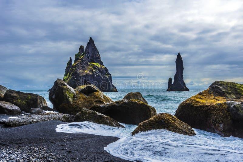 Reynisdrangar  basalt sea stacks  viewed from Reynisfjara beach seashore. Atlantic Ocean coast of Southern Iceland. Reynisdrangar basalt sea stacks viewed from royalty free stock images