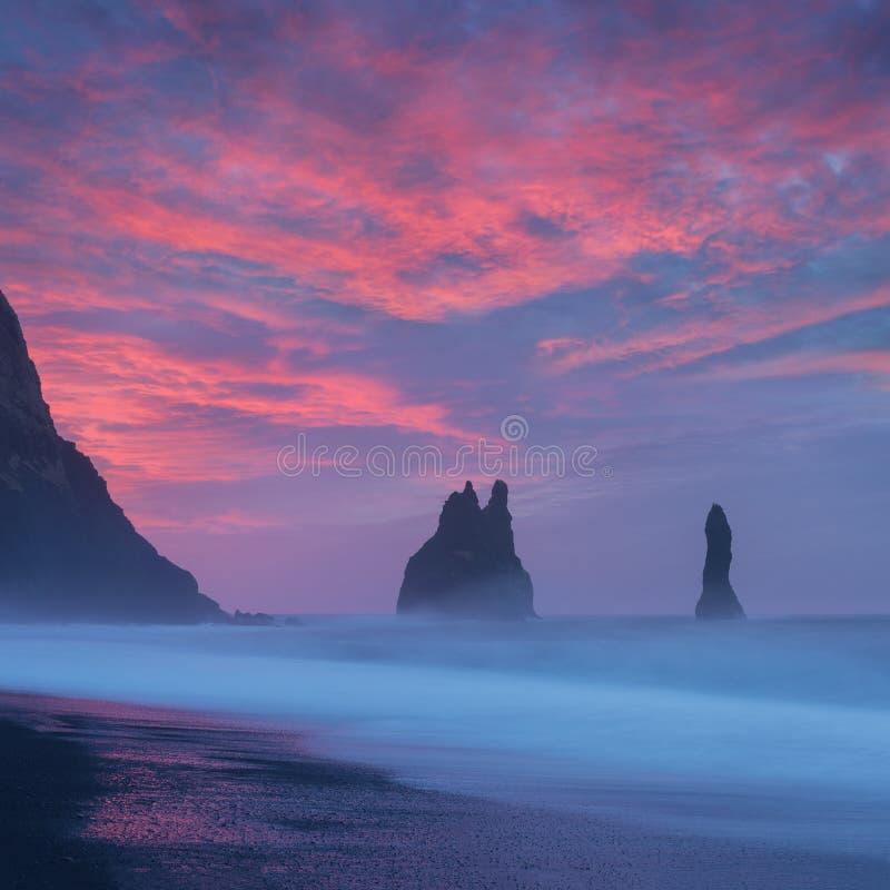 Reynisdrangar es pilas volcánicas del mar del basalto situadas debajo de los acantilados de la montaña Reynisfjall cerca del pueb foto de archivo libre de regalías