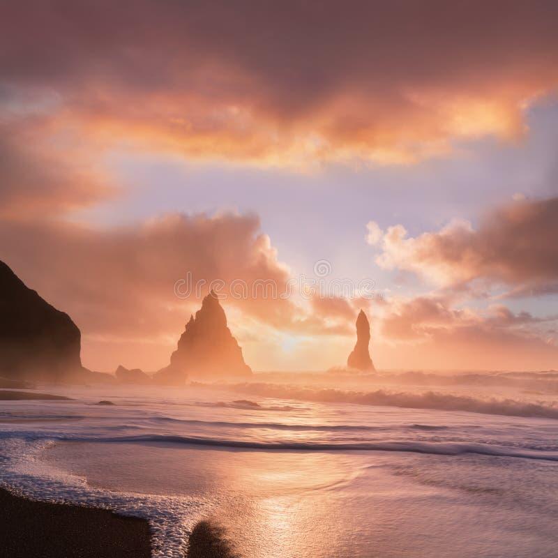 Reynisdrangar es pilas volcánicas del mar del basalto situadas debajo de los acantilados de la montaña Reynisfjall cerca del pueb foto de archivo
