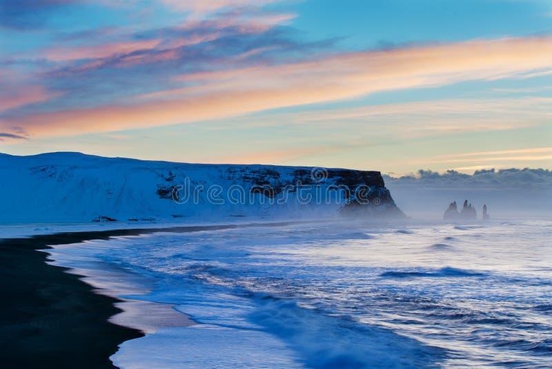 Reynisdrangar es pilas volcánicas del mar del basalto situadas debajo de los acantilados de la montaña Reynisfjall cerca del pueb imagen de archivo