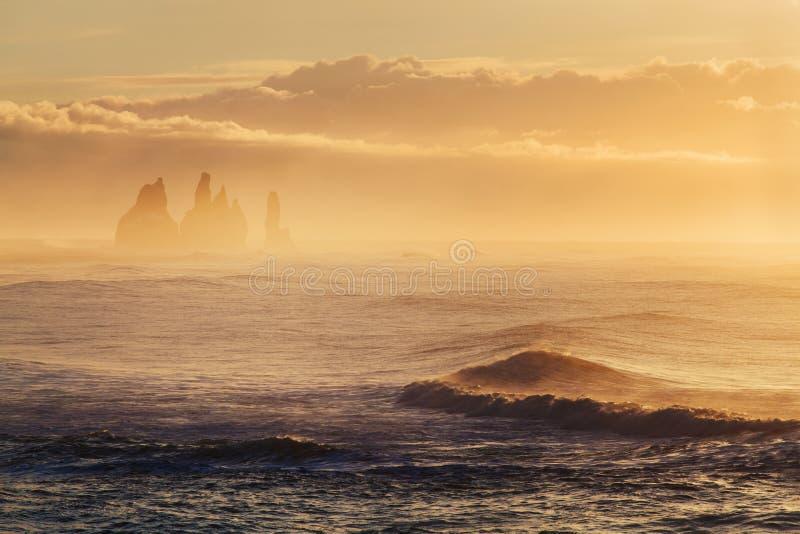 Reynisdrangar es pilas volcánicas del mar del basalto situadas debajo de los acantilados de la montaña Reynisfjall cerca del pueb imagenes de archivo