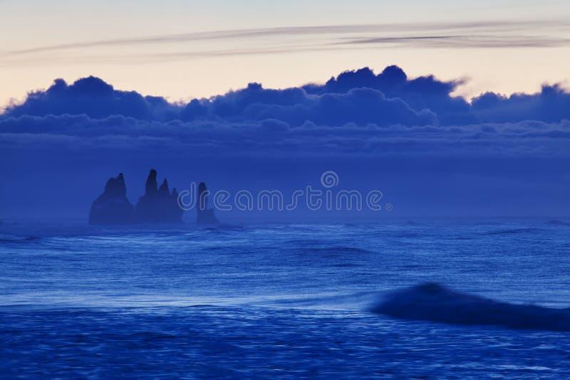 Reynisdrangar es pilas volcánicas del mar del basalto situadas debajo de los acantilados de la montaña Reynisfjall cerca del pueb imagen de archivo libre de regalías