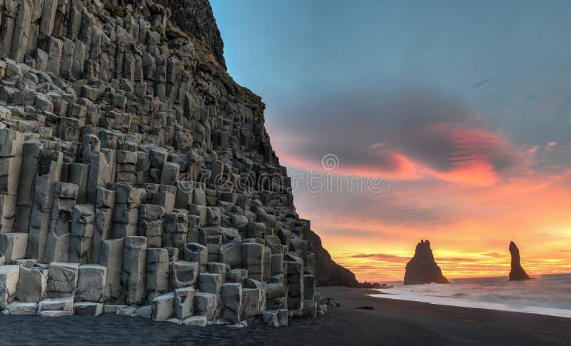 Reynisdrangar on Reynisfjara Beach. Wide view of Reynisdrangar rock formations on Reynisfjara Beach at sunrise, Halsanefhellir, Iceland stock photography