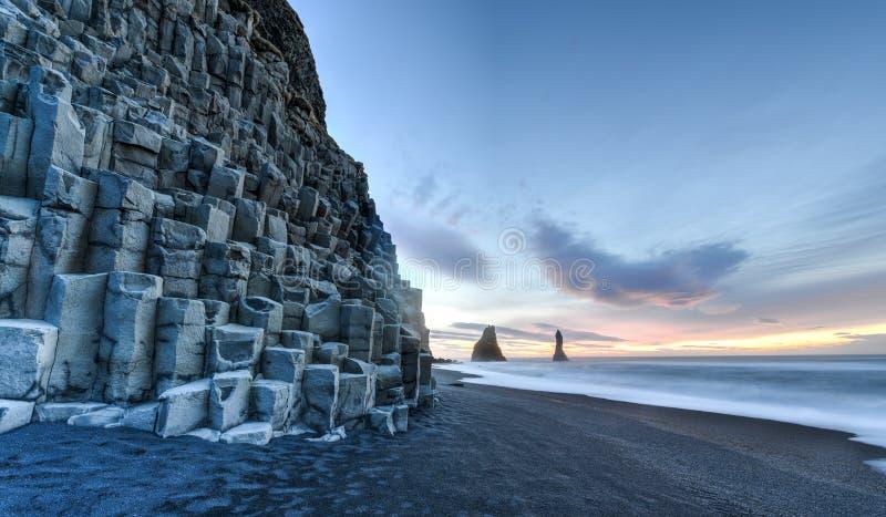 Reynisdrangar on Reynisfjara Beach. Wide view of Reynisdrangar rock formations on Reynisfjara Beach at sunrise, Halsanefhellir, Iceland stock image