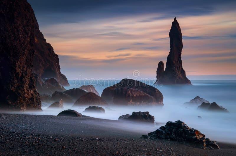Reynisdrangar rocks sunset. Reynisdrangar rocks on coastline of Reynisfjara black beach, Iceland royalty free stock photo