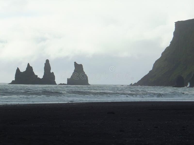 Reynisdrangar, rocks in the sea off the Reynisfjara black beach in Iceland. Reynisdrangar, rocks rising from the sea off the Reynisfjara black beach in Iceland royalty free stock photos