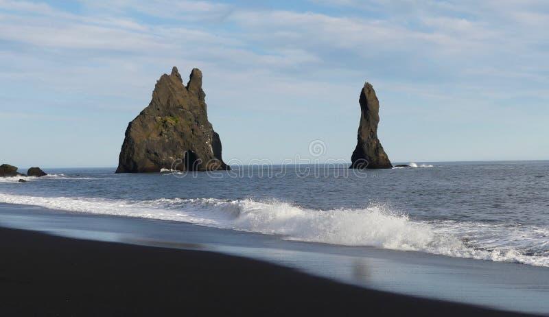 Reynisdrangar, is basalt sea stacks. Reynisdrangar is situated near by black sand beach and Vík i Myrdál village royalty free stock photos