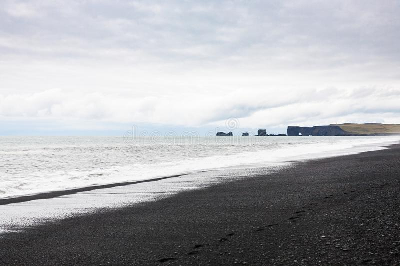 Reynisfjara Beach and view of Dyrholaey cape. Travel to Iceland - Reynisfjara Beach and view of Dyrholaey cape in Iceland, near Vik I Myrdal village on Atlantic royalty free stock photo