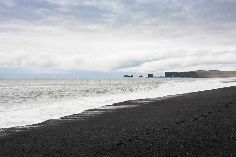 Reynisfjara Beach and view of Dyrholaey cliff. Travel to Iceland - Reynisfjara Beach and view of Dyrholaey cliff in Iceland, near Vik I Myrdal village on royalty free stock photos