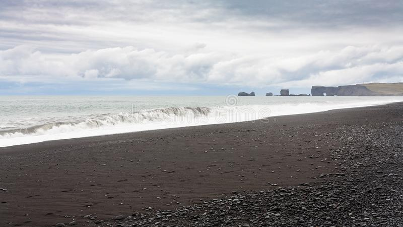 Reynisfjara Beach and view of Dyrholaey peninsula. Travel to Iceland - Reynisfjara Beach and view of Dyrholaey peninsula in Iceland, near Vik I Myrdal village on royalty free stock photos