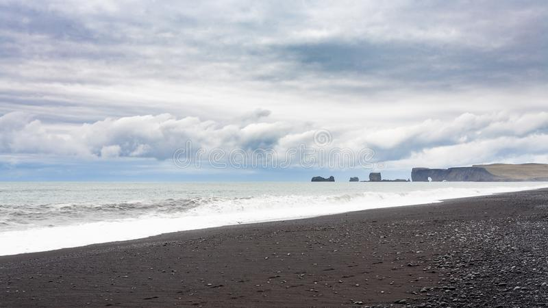 Reynisfjara Beach and view of Dyrholaey promontory. Travel to Iceland - Reynisfjara Beach and view of Dyrholaey promontory in Iceland, near Vik I Myrdal village royalty free stock images