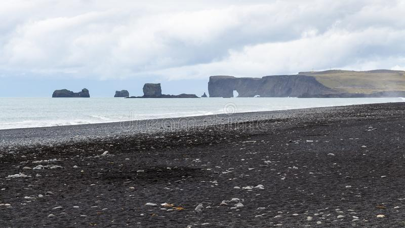 Reynisfjara black beach and view of Dyrholaey cape. Travel to Iceland - Reynisfjara black sand beach and view of Dyrholaey cape in Iceland, near Vik I Myrdal royalty free stock images