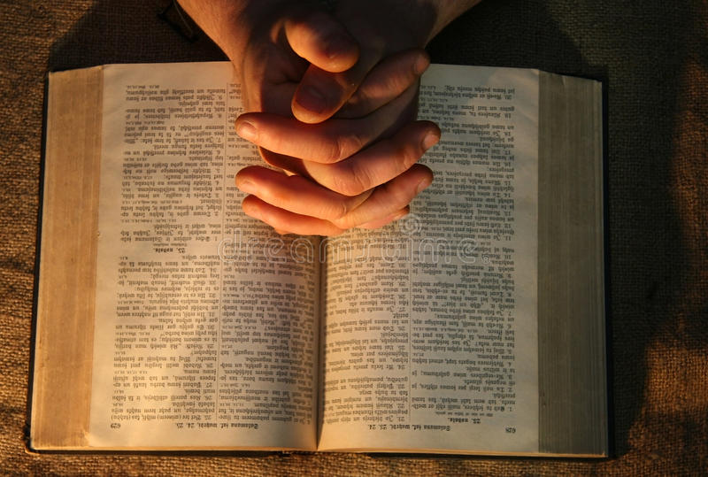 Rezando a Bíblia das mãos imagem de stock royalty free