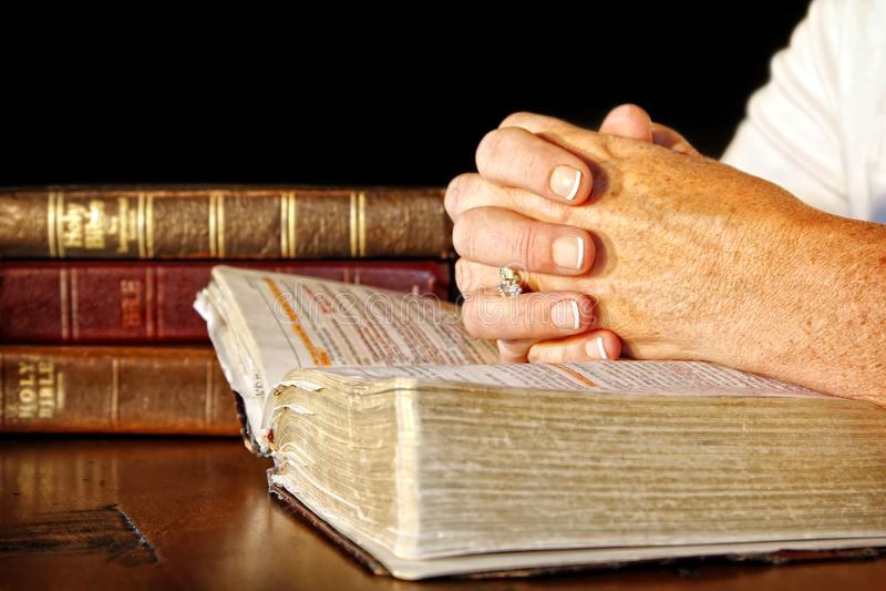Rezando a mulher com as Bíblias Sagradas imagens de stock royalty free