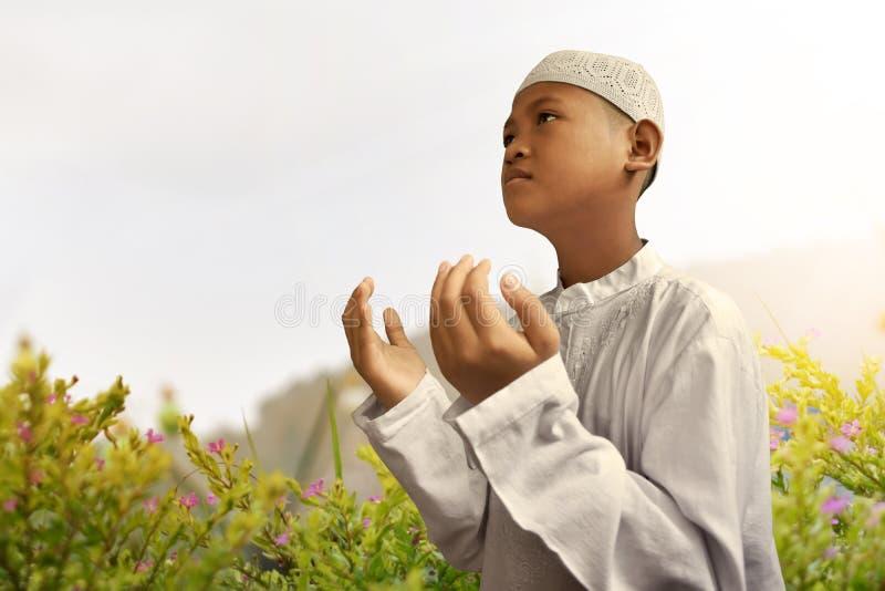 Rezar asiático da criança dos muçulmanos imagem de stock