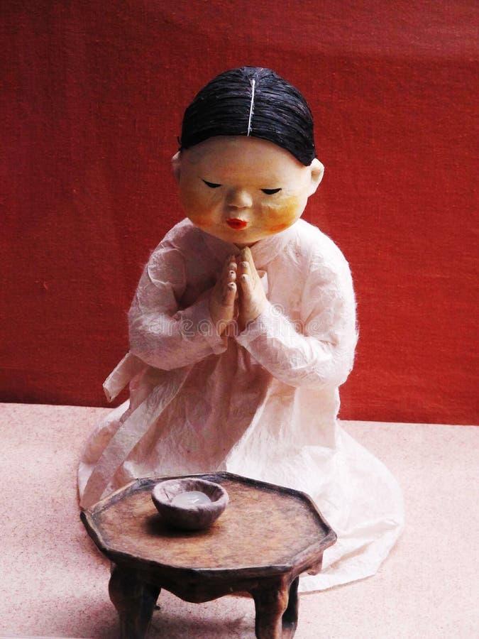Rezar da boneca da menina foto de stock royalty free