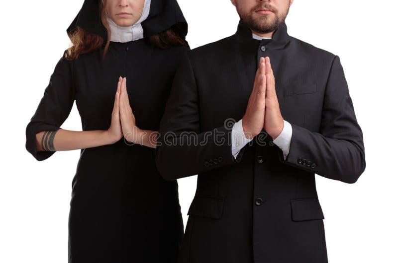 Rezar da freira e do padre isolado em um fundo branco imagens de stock