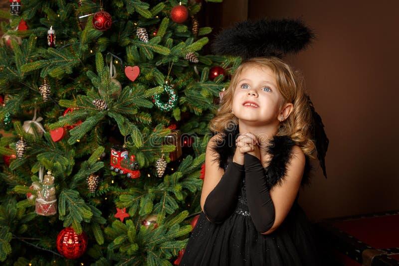 Rezar uma menina em um traje preto do anjo, olhando com esperança para a paz Infância e paz felizes Natal, ano novo imagem de stock royalty free