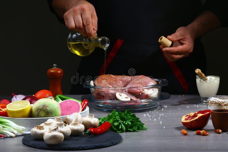 Rezept für das Kochen des Kaninchenfleisches Auslaufendes Öl des Chefs auf Kaninchenfleisch, Garprozess, Restaurantkonzept stockfotos