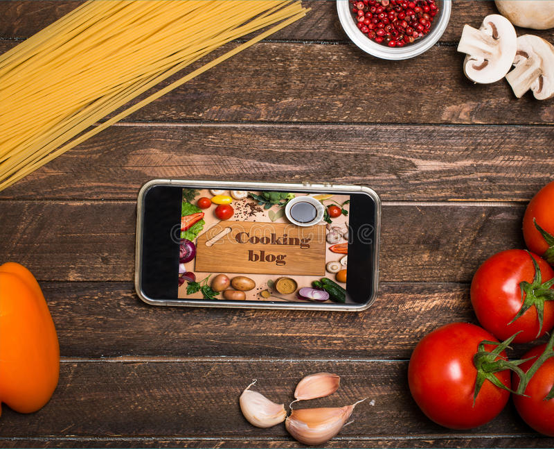 Rezepte online kochen: Kochen des Blogs auf einem Smartphoneschirm, ing lizenzfreie stockfotografie