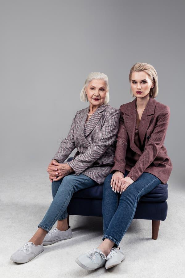 Rezolutne poważne kobiety siedzi na małej kanapie podczas gdy będący ubranym surowe kurtki zdjęcie royalty free