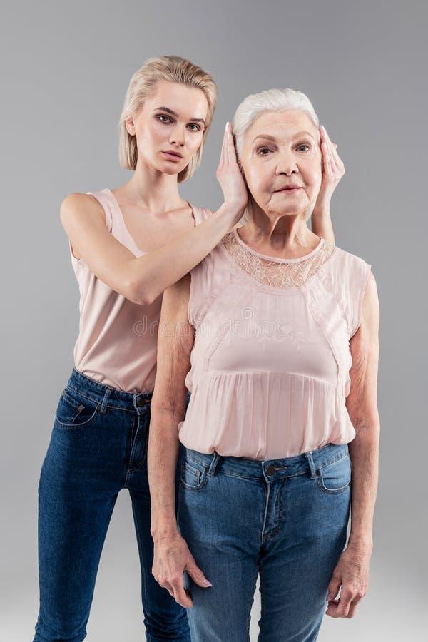 Rezolutny blondynka opiekunu domykanie w górę ucho nieporuszona matka zdjęcie royalty free