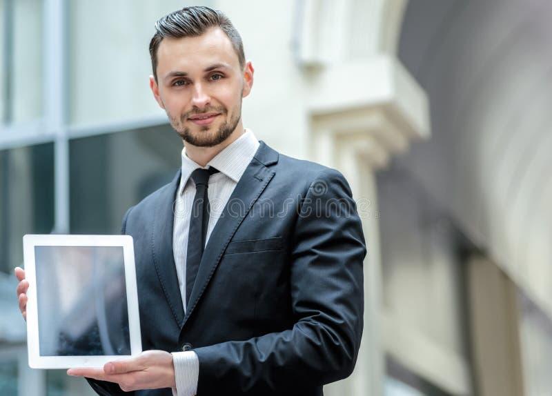 rezultaty Pomyślny biznesmen trzyma pastylkę w formalnej odzieży obrazy royalty free
