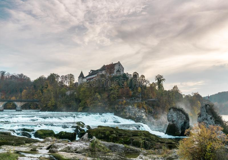 Nightfall and dusk on the Rhine Falls and Rhine River with an illuminated castle building on the water royalty free stock photos
