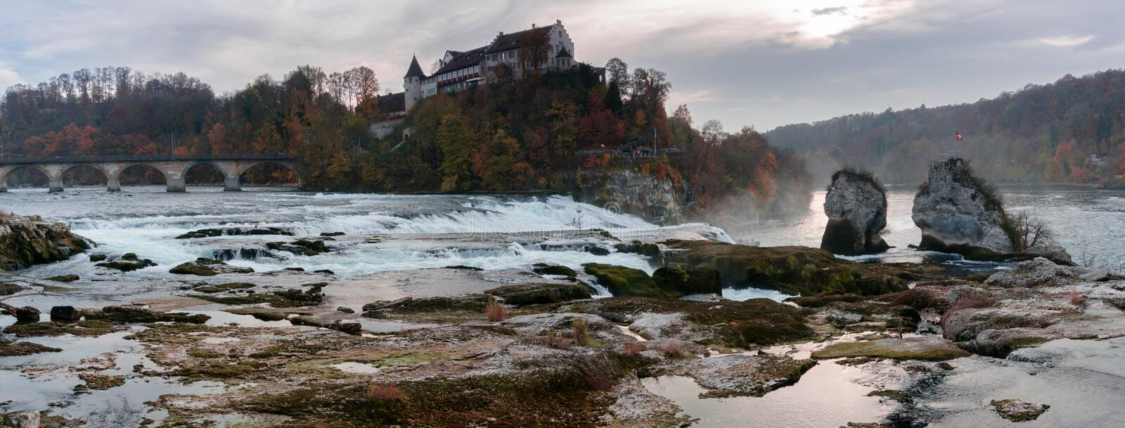 Nightfall and dusk on the Rhine Falls and Rhine River with an illuminated castle building on the water stock images