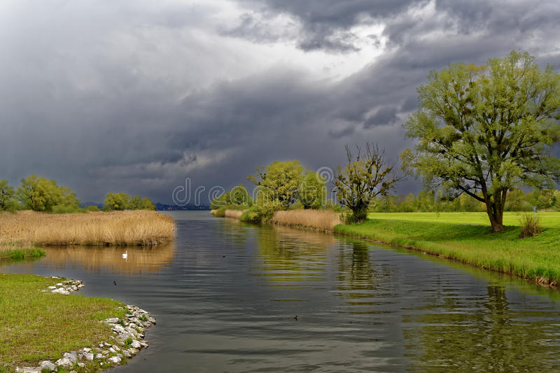 River delta lake landscape by dark clouds in spring royalty free stock photography