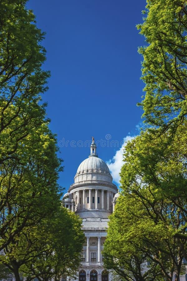 Rhode Island State House mellan träd mot blå himmel arkivbilder