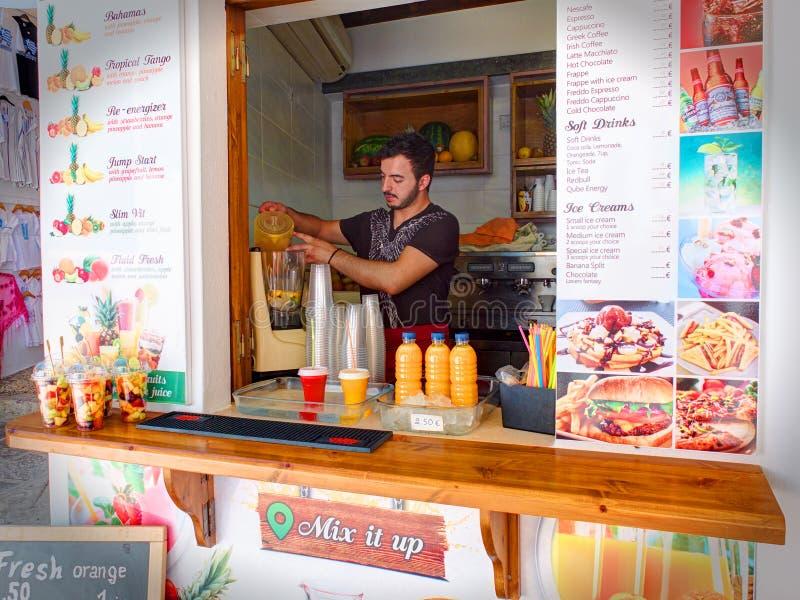 RHODES Ö, LINDOS, GREKLAND, JUNI, 25, 2015: Den grekiska bartendermannen i litet gatakafé med nya fruktsafter, mjölkar och frukts arkivfoton