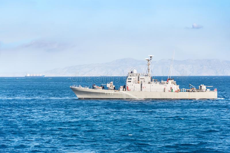RHODES, GREECE – SEPTEMBER 21 2017: HS Ormi – Greek gunboat P230 leaves port in city of Rhodes. Coast of Turkey in background stock photo
