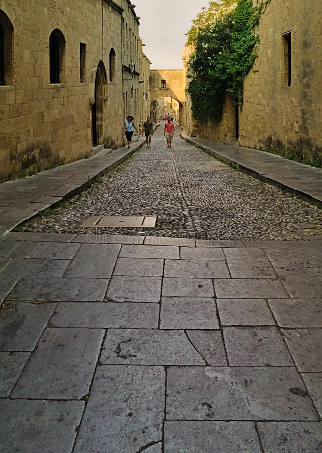 People walking on old town cobblestone alley between ancient buildings stock photo