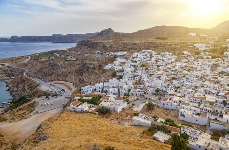 Rhodes Island in Greece. City on hill with white residential buildings and touristic hotels. Road with heavy traffic among coast. Seascape and mountains stock photos