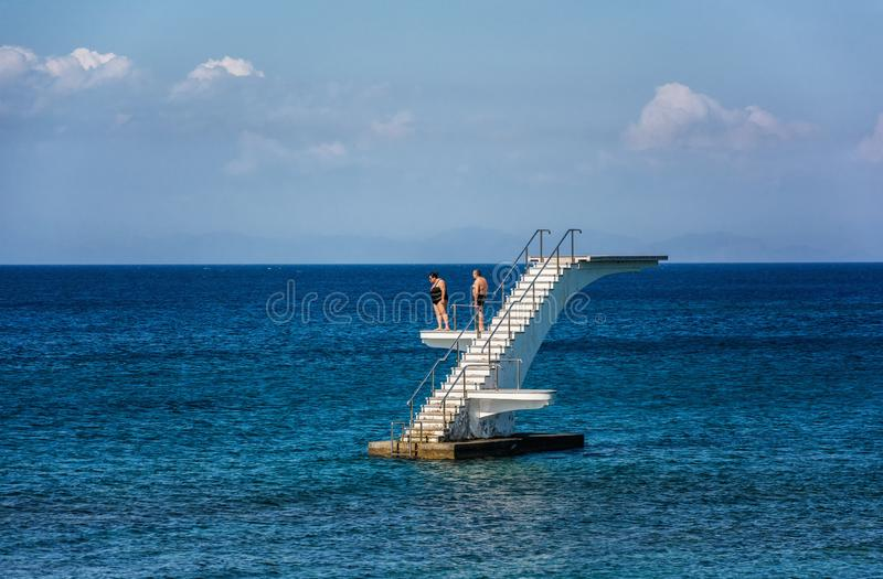 RHODES ISLAND , Greece - 5 JUNE 2014: Couple thinking about diving to the sea. Dodekanes island of Greece royalty free stock image