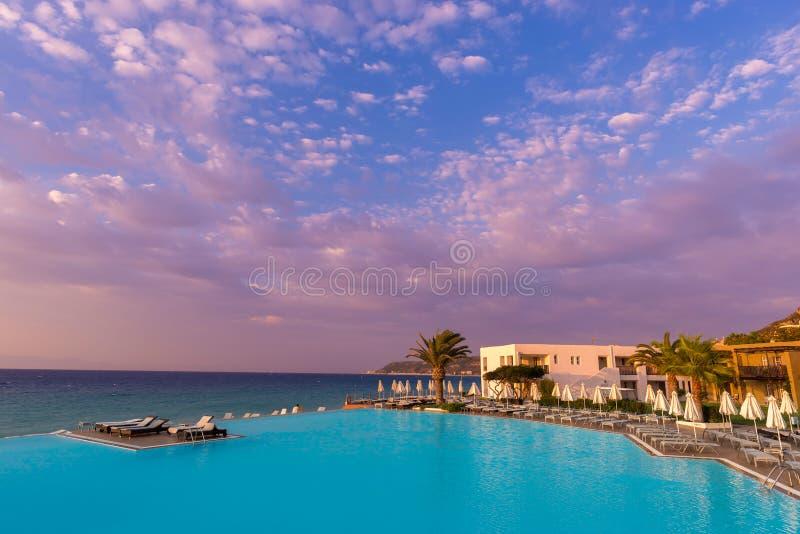 Rhodos, Grèce - août 2016 : Beau coucher du soleil au-dessus d'une station balnéaire avec la piscine infinie dans le golfe d'Ixia photographie stock